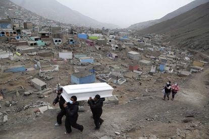 Los trabajadores del cementerio Mártires 19 de Julio trasladan un ataúd a las afueras de Lima.