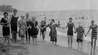 Un grupo de hombres y mujeres en la playa de Arenys de Mar, alrededor de 1920. / Arxiu Fotogràfic Centre Excursionista de Catalunya.
