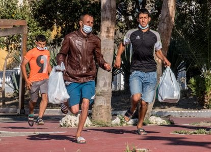Tres marroquíes que viven en las calles de Ceuta huyen de una redada policial, el pasado 23 de mayo.