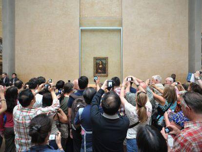 Decenas de turistas fotografían la Mona Lisa en el Louvre.