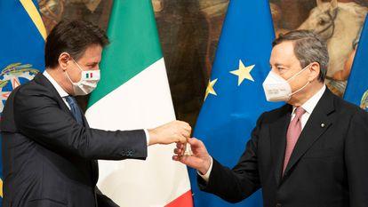 El nuevo primer ministro, Mario Draghi, recibe de su predecesor, Giuseppe Conte, una campanilla de plata como símbolo del traspaso de poderes, este sábado en Roma.