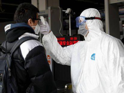 Un trabajador con traje de protección utiliza un termómetro para medir la temperatura de un viajero en la estación de metro de Xizhimen en Pekín.