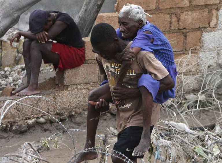 Un hombre ayuda a una anciana tras el paso del huracán Hanna y antes de la llegada del Ike.