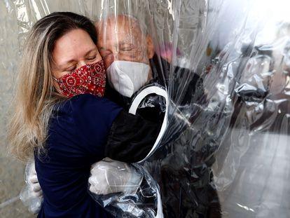 Una mujer abraza a su padre, de 82 años, en una residencia de ancianos en la ciudad de São Paulo (Brasil), el pasado 23 de diciembre.