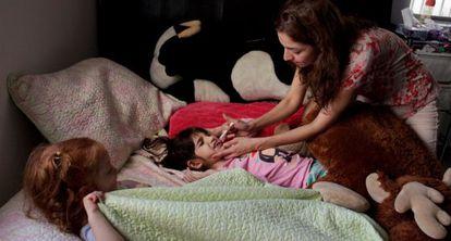 La madre de Graciela Elizalde da la medicación a su hija.