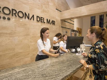 Sabina Urraca atiende a una cliente en la recepción de un hotel de Benidorm.