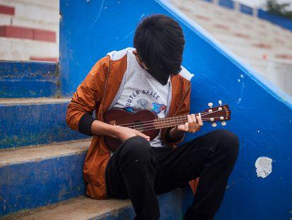 Andre (nombre ficticio), de 14 años, toca el ukelele en las gradas de un estadio deportivo remodelado en Carabayllo, un distrito en el norte de Lima, Perú, mientras espera la hora de su cita programada para ser atendido en el Centro Comunitario de Salud Mental.