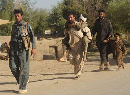 Un hombre lleva a su hijo herido durante el ataque talibán en Pul-i-Alam, capital de Logar.