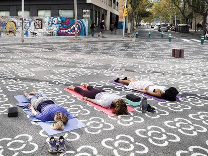 Vecinas de Poblenou practican yoga en una de las intersecciones de la 'supermanzana'.