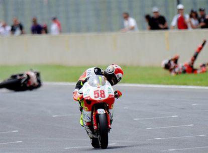 Marco Simoncelli mira a Héctor Barberá, caído en el suelo tras su choque con el piloto italiano.