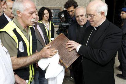 El arzobispo de Compostela (derecha) examina ante la policía el estado del códice. Debajo, detalle del Codex Calixtinus.