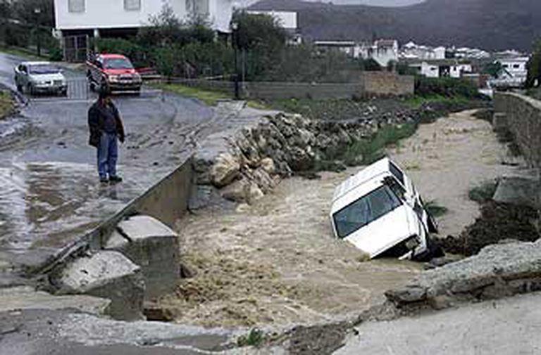 Un hombre observa el coche del hombre desaparecido en Riogordo, que fue arrastrado por un arroyo que pasa por el municipio.