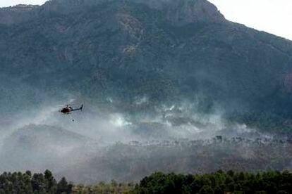 Unos doce medios aéreos (avionetas y helicópteros bombarderos) colaboran con la extinción del fuego en el Parque Natural de Els Ports