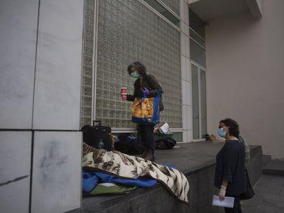 Dos voluntarias conversan con Tina, una mujer sin hogar que vive en las proximidades del MACBA, en Barcelona.