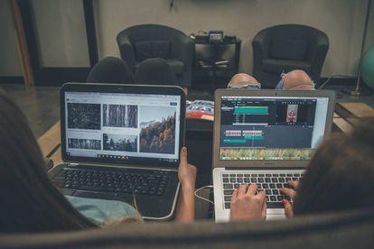 Dos personas navegan por Internet con sus ordenadores portátiles.