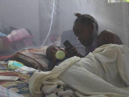 Una joven madre y su hijo se recuestan bajo una red para mosquitos en un refugio luego que el huracán María impactara a Dominica