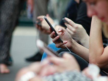 Adolescentes usando sus teléfonos móviles.
