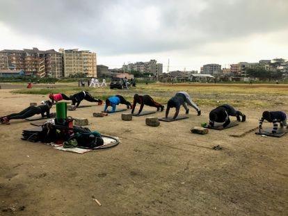 Media docena de miembros del 'Team Tina' hace flexiones en el espacio al aire libre habilitado como gimnasio en el barrio de Tena, en Nairobi, Kenia.