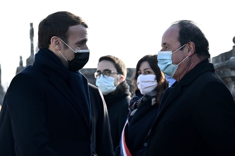 French President Emmanuel Macron greets his predecessor, François Hollande, during the ceremony for the 25th anniversary of the death of François Mitterrand