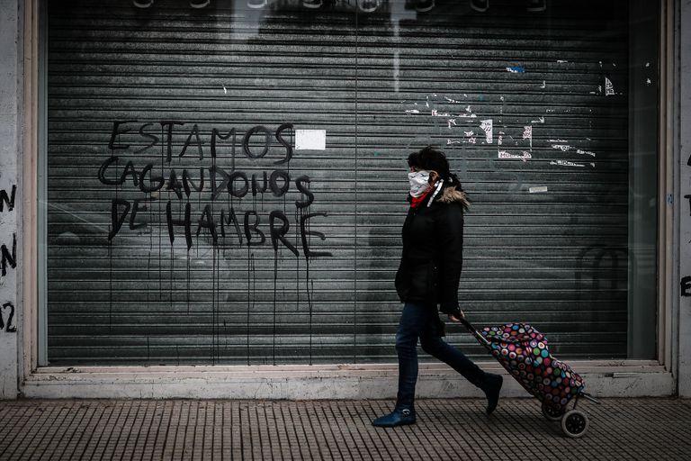 Una mujer camina frente a un grafiti en ciudad de Buenos Aires, en junio de este año.