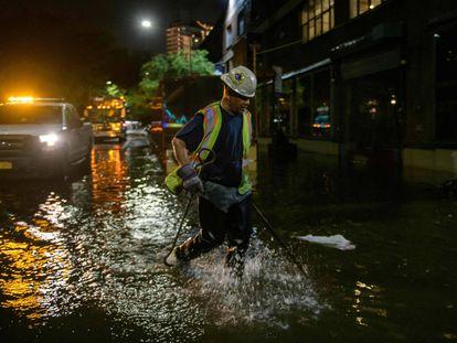 Un trabajador desbloquea los desagües en una calle afectada por las inundaciones en Brooklyn, Nueva York, a principios del 2 de septiembre de 2021, cuando las inundaciones repentinas y las lluvias récord traídas por los restos de la tormenta Ida barrieron el área.