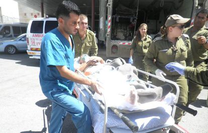 Personal médico del hospital de Ziv y soldados israelíes acompañan a un herido sirio.