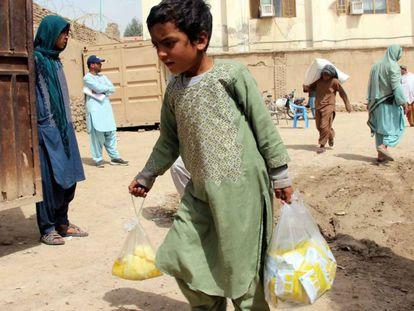 Un niño sostiene bolsas con ayuda entregada a varias familias afganas afectadas por inundaciones, en Kandahar.