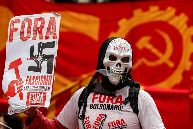 Un hombre encapuchado sostiene un cartel durante una manifestación en contra del presidente Jair Bolsonaro, este domingo, en Sao Paulo.