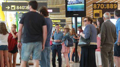 Varios pasajeros esperan en la T4 del aeropuerto de Barajas.