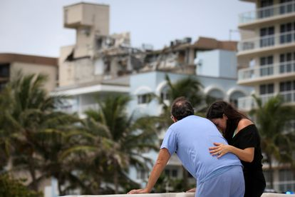 A couple in front of the partially collapsed building in Surfside, Miami.