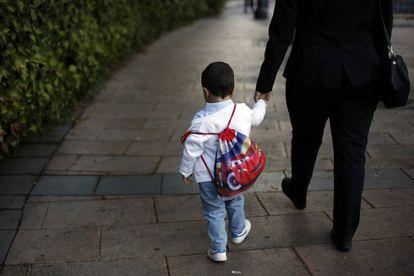 Un niño con su mochila camina de la mano de su madre camino del colegio público Reina Victoria de Madrid.