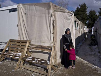 Rania Askar, de Deir el-Zour (Siria), posa con su hija de cuatro años, Maya, frente a su refugio en el campamento de Ritsona (Grecia).