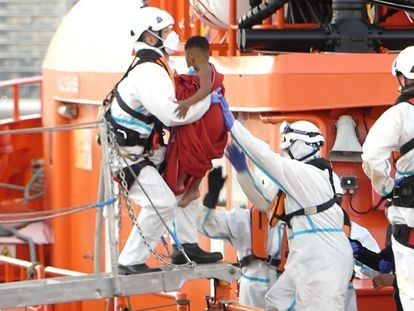 Un miembro de la Cruz Roja ayuda a bajar del barco a un niño migrante en el puerto de Arguineguín (Gran Canaria) el pasado 17 de marzo.