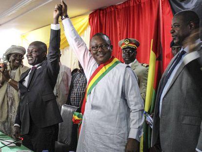 Embalo, vestido de blanco, alza su brazo en señal de victoria junto a su predecesor, José Mario Vaz, durante su autoproclamación como presidente.