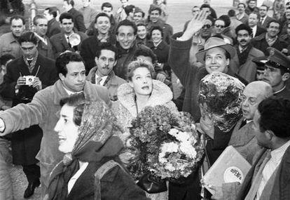 Enrique Herreros hijo, con el brazo, abre camino entre el gentío a Romy Schneider el 15 de enero de 1957 a su llegada al aeropuerto de Barajas para promocionar 'Sissi'. A la derecha, con la caja de la distribuidora Dipenfa, Enrique Herreros padre.