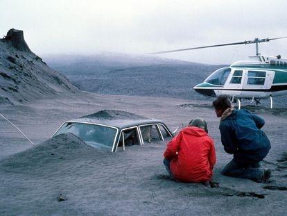 Geólogos observan un coche semienterrado por la ceniza de la erupción del monte Santa Helena (noroeste de EE UU), en 1980.