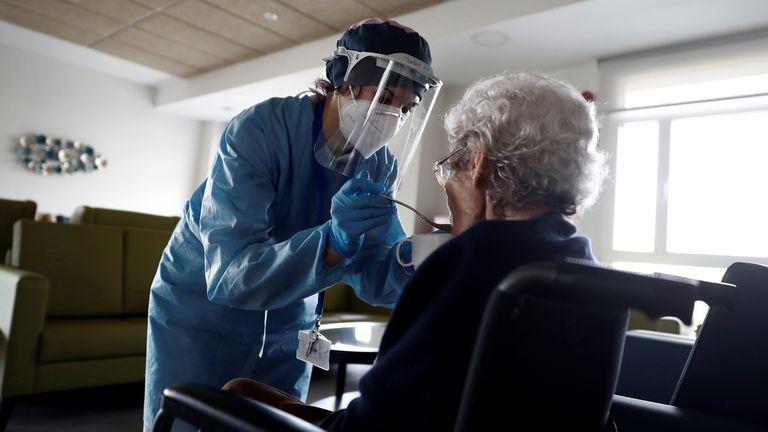 Una cuidadora ayuda a comer a una anciana en una residencia del barrio madrileño de Villaverde, en Madrid.