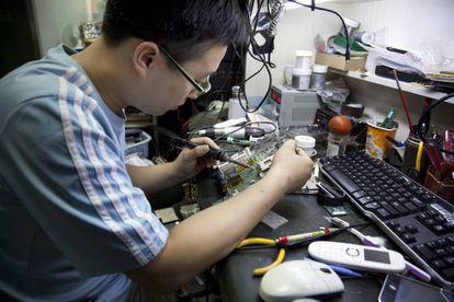 Un hombre repara unos circuitos en Beijing, China.