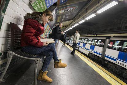 Una joven lee mientras espera el metro, ayer en la estación de Alonso Martínez, en Madrid.