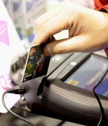 Una persona paga con tarjeta, en un negocio de Buenos Aires.