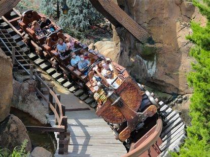 Personas con mascarilla en una montaña rusa de Walt Disney World este fin de semana en Orlando, Florida.
