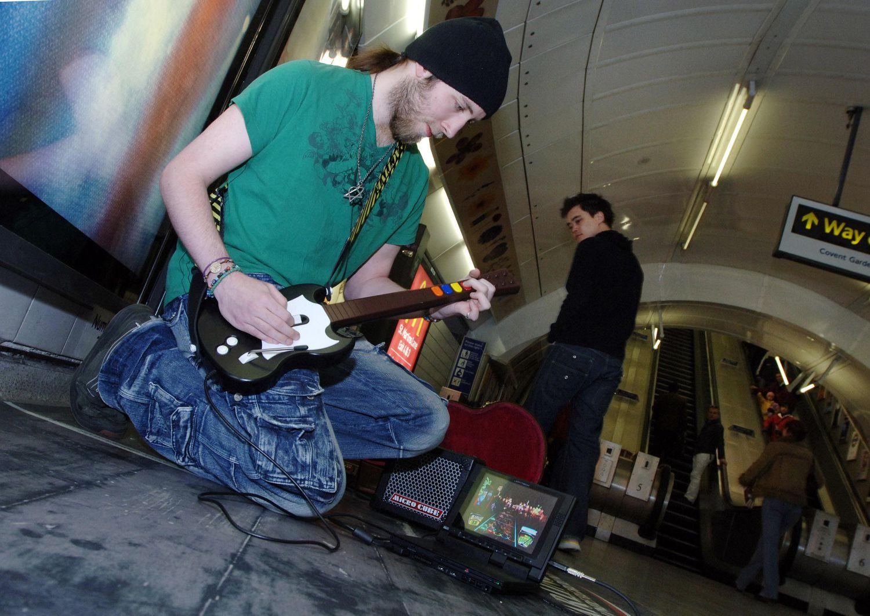 Luke Albiges toca en Leicester Square en Londres usando el Guitar Hero de la PlayStation 2