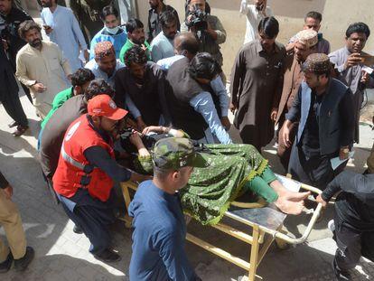 Varios hombres trasladan a una herida tras el terremoto en Harnai, Paquistán.