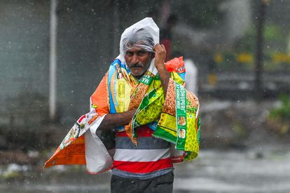 A man protects himself with plastic on a street in Amreli, Gujarat, this Tuesday.