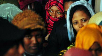 Mujeres y niños que huyeron de Libia son transportados por autobús a su llegada a Lampedusa ayer