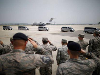 Soldados estadounideses frente a una fila de vehículos que transportas los cuerpos de 55 militares fallecidos en la Guerra de Corea.