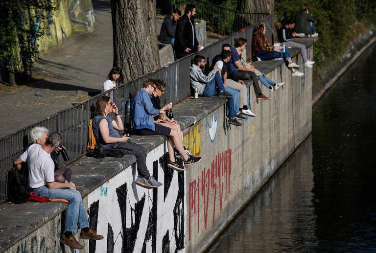 Gente pasea, charla y mira el móvil en Berlín, durante la pandemia del coronavirus.