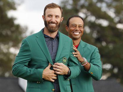 Dustin Johnson con la chaqueta verde que le entrega Tiger Woods.