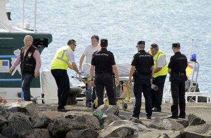 Varios policías rodean el cuerpo del inmigrante fallecido, el día 13.
