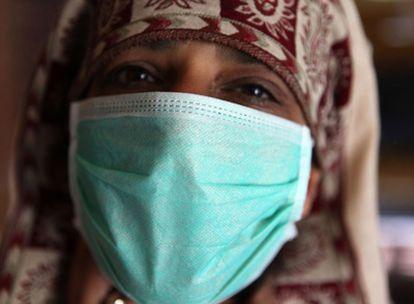 Una mujer se protege con una mascarilla del virus de la gripe A en Kabul.